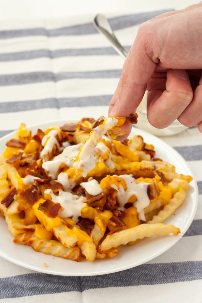 Bacon Ranch Cheese Fries - A sharp cheddar cheese sauce, crumbled bacon, and ranch dressing for dipping take these cheese fries to a new level.