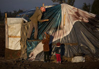 © UNICEF Lebanon/2013/Ramoneda Children help their father repair the family's tent shelter in a makeshift encampment in Akkar region. In these camps, tents might be pitched in mud, with children scavenging for food.
