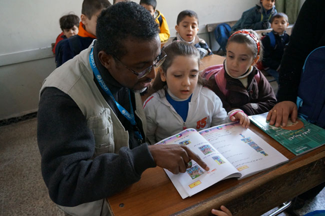 Mr. Musse assists a girl as she reads from her textbook, in her classroom at a public primary school in Homs. © UNICEF/NYHQ2013-0128/Morooka