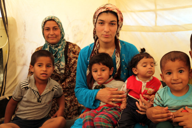 Shereen, 25, (right) sits in her tent in Kawergosk refugee camp in northern Iraq with her children Yasmine, 2, and Ayenda, 7 months. Her sister sits next to her. ©UNICEF/Iraq-2013/Niles