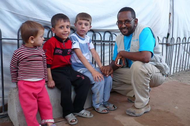 UNICEF Iraq South Zone Chief Maulid Warfa with children in Baherka refugee camp in Erbil, northern Iraq. © UNICEF/Iraq-2013/Groote