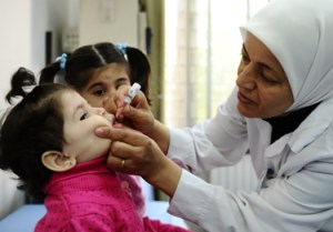 A health worker administers polio vaccine to a child at the centre, as part of a vaccination campaign under way in the Syrian Arab Republic. The campaign targets 2.4 million children with life-saving vaccinations. © UNICEF Syrian Arab Republic/2013/Sanadiki