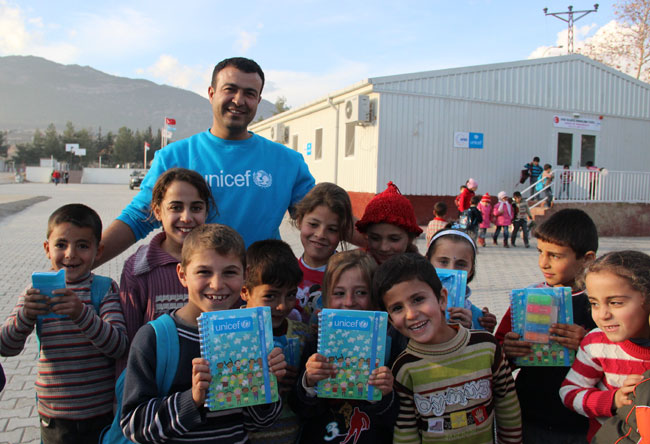Students celebrate the end of school term holding report cards and new pen and paper sets. ©UNICEF/Turkey-2014/Yurtsever