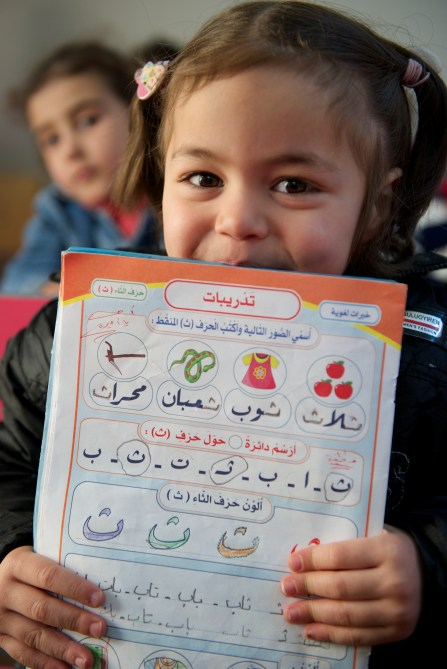 A child proudly holds up her Arabic workbook.