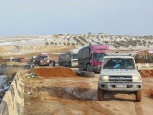 قافلة إمدادات إنسانية للأمم المتحدة تفاوض القائمين على نقطة تفتيش أثناء عبور خط القتال نحو ريف إدلب