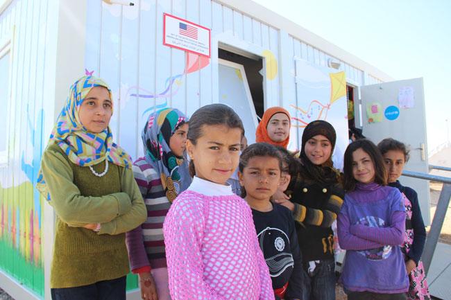 رزان وأصدقاؤها يقفون خارج المساحة الصديقة للأطفال التي تقوم عليها اليونيسف في مخيم ساريكام للاجئين في أضنة، تركيا