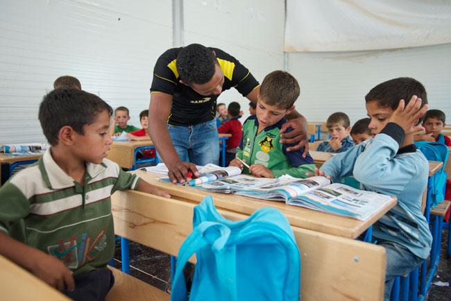 معلم يساعد طالباً في الصف الأول في أحد الصفوف التي تدعمها اليونيسف في مخيم الزعتري للاجئين السوريين في الأردن.