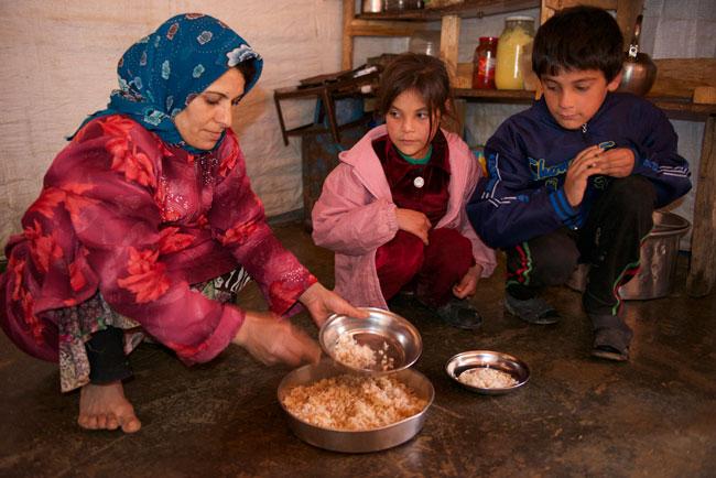 عالية (في الوسط) تتناول وجبة الإفطار قبل الذهاب إلى المدرسة في مخيم الدلهمية