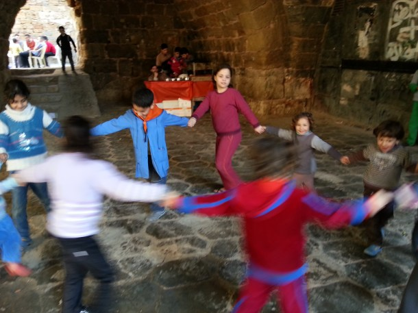 Children hold hands and dance in a circle