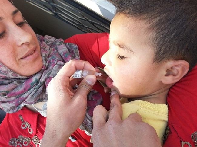 أم تراقب ابنها وهو يتلقى لقاح ضد شلل الأطفال خلال حملة التلقيح التي تدعمها اليونيسف في دير الزور. ©UNICEF/Syria-2014/Najem