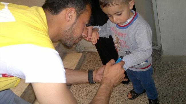 متطوع في ديرالزور يضع علامة على إصبع طفل بعمر سنتين تلقى لتوه قطرات من اللقاح ضمن حملة التطعيم الجارية في المنطقة. ©UNICEF/Syria-2014/Najem