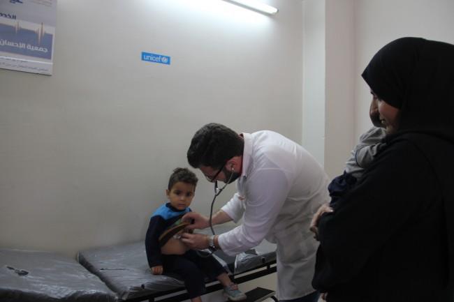 طبيب يفحص طفلا في عيادة صحية تدعمها اليونيسيف في مدينة حلب