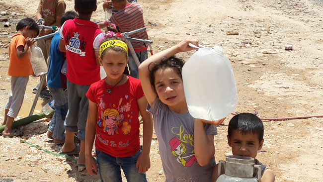 Fatima  carries a water while other children queue at a community water point at a shelter in Aleppo city. © UNICEF Syria/2014/Kumar Tiku