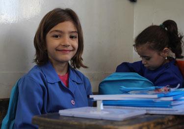 © UNICEF Syrian Arab Republic/2014/Rashidi A third grade girl with her new bag and stationery supplies
