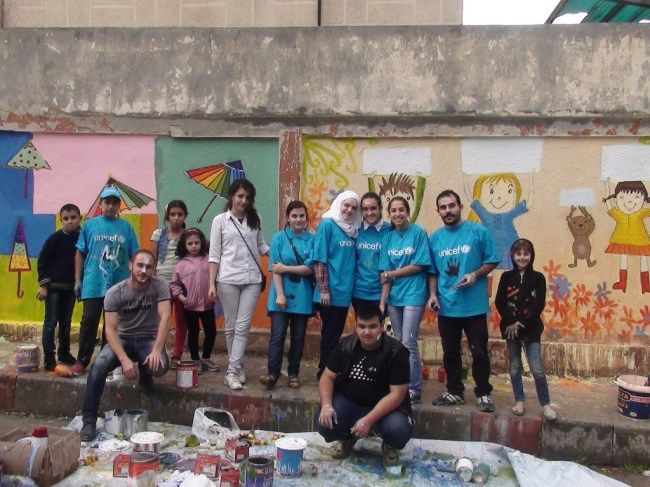 Adolescent volunteers painting the external perimeter wall of Akrama Al Muhdatha school. ©UNICEF/Syria-2014/UNICEF Homs Staff