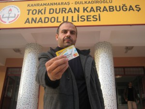 "Teacher Raid from Hama, posing with the PTT card, says: ""This incentive has encouraged me to be more efficient. The financial problems that bothered me have been relieved. Now I can focus better on teaching."" @UNICEF/Turkey 2015/Yurtsever"