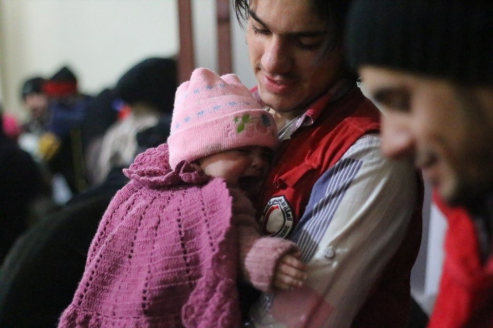 SARC volunteer soothes a baby girl after injecting routine vaccine at SARC clinic in Douma- Damascus Suburbs ©UNICEF/Syria/2015/Hussamsyr