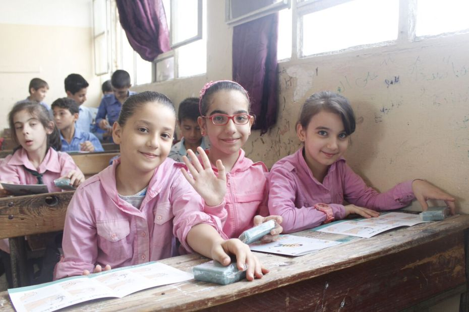 ©UNICEF/ Syria 2015/ Yasmine Saker. 5th graders Ghinwa (middle), and her two best friends Bissan and Batoul after receiving their UNICEF bars of soap and a brochure explaining the best practices of hand washing.