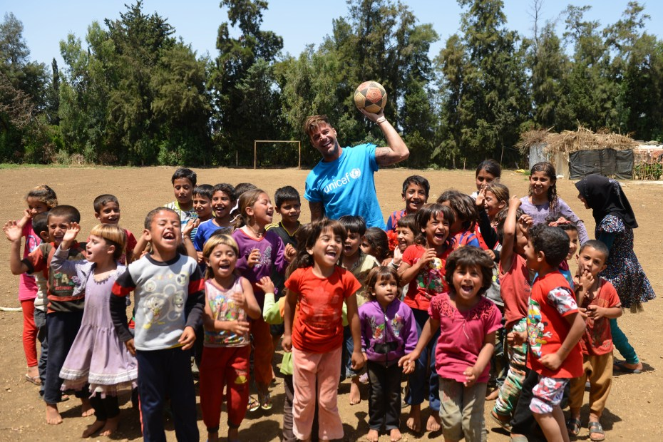 On 1 June 2016, UNICEF goodwill ambassador Ricky Martin plays football with Syrian refugee children at Al-Hissa informal refugee settlement in northern Lebanon.   World-renowned singer and UNICEF Goodwill Ambassador Ricky Martin calls for increased focus on safeguarding the futures of millions of children affected by the Syria conflict, whose lives have been shaped by displacement, violence and a persistent lack of opportunities. During the two-day visit to Lebanon from 1-2 June 2016, Martin also witnessed how UNICEF is working to provide protective environments for children and adolescents where they can play and receive the support they need to get back into formal education. In Lebanon's Bekaa valley and Akkar, Martin participated in recreational activities for children at safe spaces in informal settlements. Additionally, he met adolescents attending life-skills training, provided by UNICEF and partners, where girls and boys are given vocational training and learning support. Around 1.1 million Syrians have sought refuge in Lebanon since the start of the crisis in 2011, more than half of them are children. Child refugees are particularly at risk of exploitation and abuse, with large numbers being left with no choice but to go out to work, rather than attend school. Child refugees are particularly at risk of exploitation and abuse, with large numbers being left with no choice but to go out to work, rather than attend school.  The deteriorating economic situation for Syrian refugees has dramatically exacerbated the problem of child labour in Lebanon. Adding to the psychological distress already affecting many of the children who have fled conflict and violence at home is the challenge associated with some of the worst forms child labour such as working on construction sites, which can cause long-term developmental and psychological damage as well as physical harm. UNICEF is working closely with the Government institutions, as well as local and international par