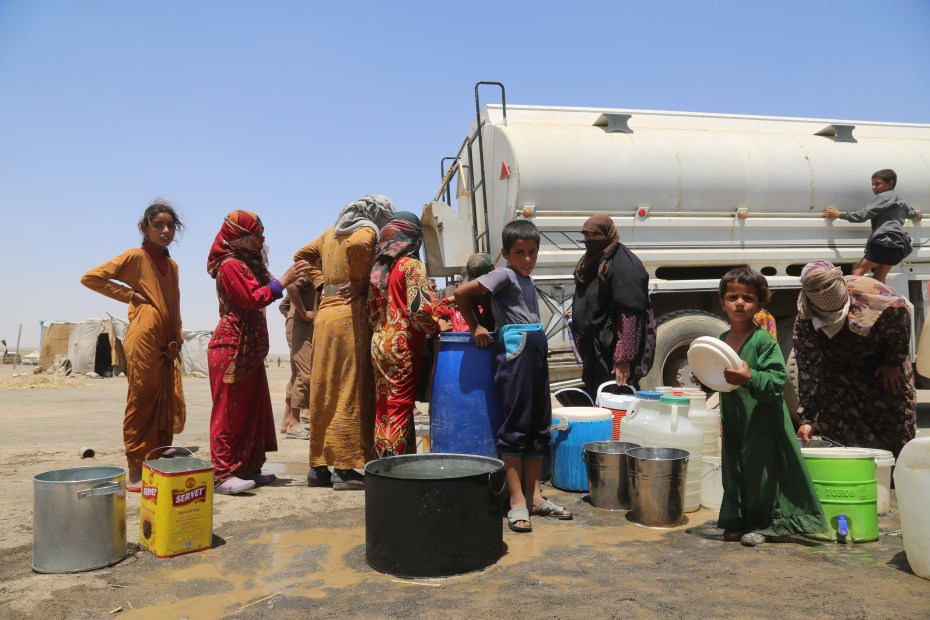 ©UNICEF/ Syria 2017/ Delil Souleiman Women and children line up to fetch water for their families in Al-Karama makeshift camp in Ar-Raqqa.  UNICEF is responding to the needs of uprooted children and their families, trucking 600,000 litres of safe drinking water daily.