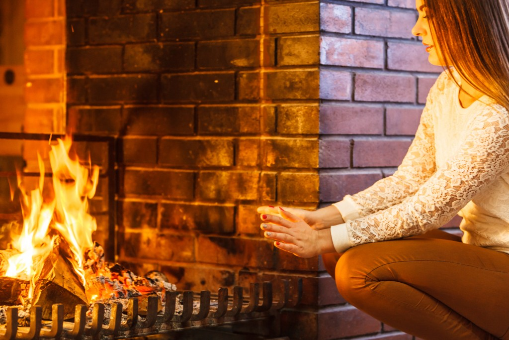 Woman warming hands up at fireplace. Young girl relaxing resting. Winter at home.