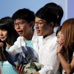 Student leader Joshua Wong (2nd L) greets candidate Nathan Law (C) as supporters share their joy after Law won in the Legislative Council election in Hong Kong, China September 5, 2016. REUTERS/Tyrone Siu