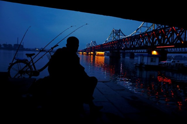 A man looks across Yalu River towards North Korea as he sits next to the bridge that connects China's Dandong, Liaoning province and North Korea's Sinuiju, September 10, 2016. REUTERS/Thomas Peter