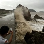 A man records waves whipping the shore before Typhoon Meranti makes a landfall on southeastern China, in Wenling, Zhejiang province, China, September 14, 2016. Picture taken September 14, 2016. REUTERS/Stringer