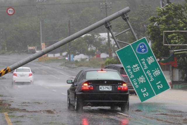 A car drives past a collapsed traffic sign, toppled by strong winds of typhoon Meranti, in Kaohsiung, Taiwan September 14, 2016. Picture taken September 14, 2016. REUTERS/Stringer