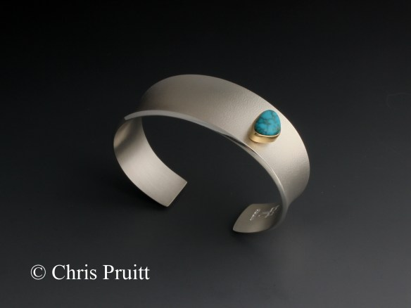 Textured, sterling silver, anticlastic bracelet with 18k gold bezel and raised Lone Mountain turquoise. Tapered at the bottom.