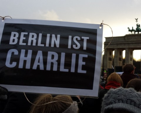 """Schild mit Text """"Berlin ist Charlie"""" vor Brandenburger Tor"""
