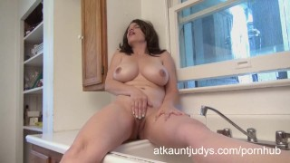 Big tit MILF Kelly Capone masturbates in the kitchen.