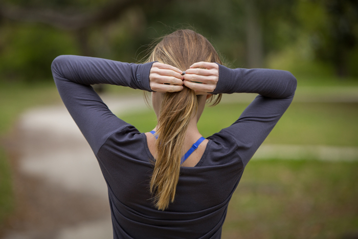 Woman Putting Hair In Ponytail for Workout