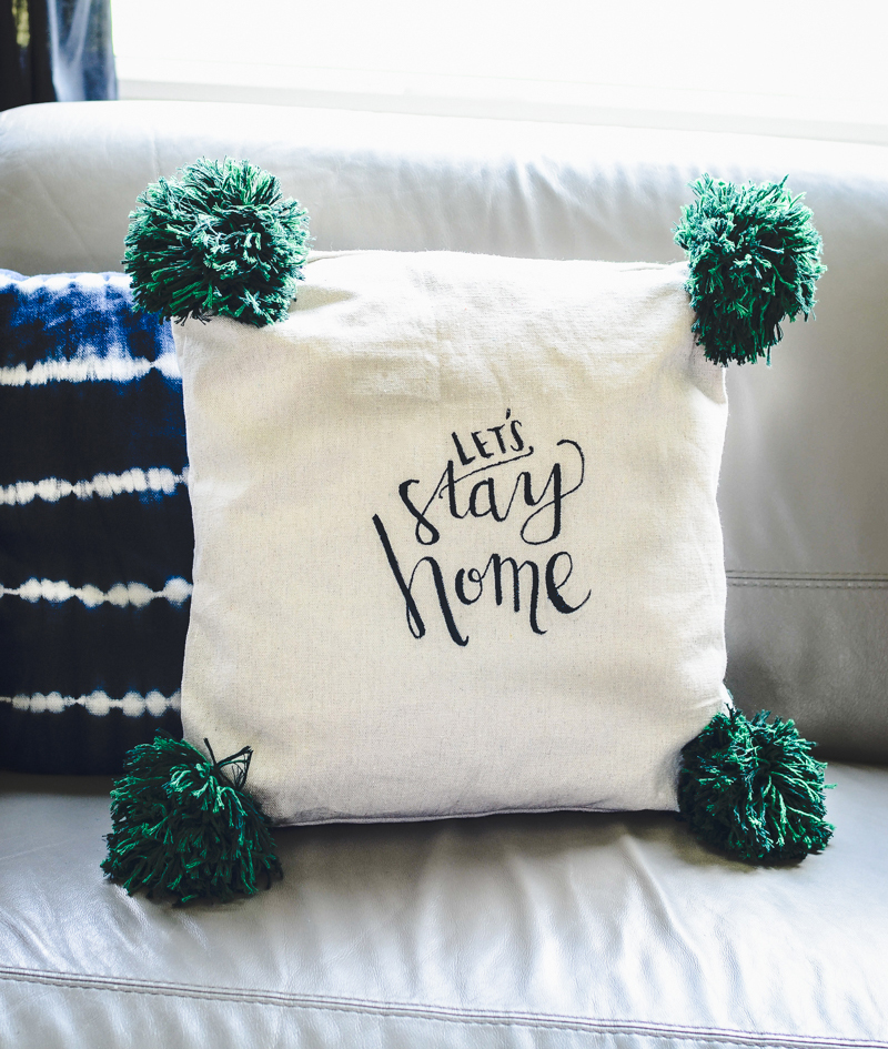 Make this fun hand lettered giant pom pom pillow!