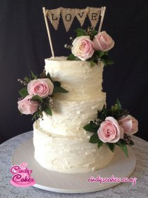 3 tier Buttercream wedding cake with pink flowers and the word love written on hessian material as the topper