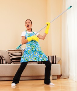 funny woman mopping floor and playing. beautiful girl playing music using mop