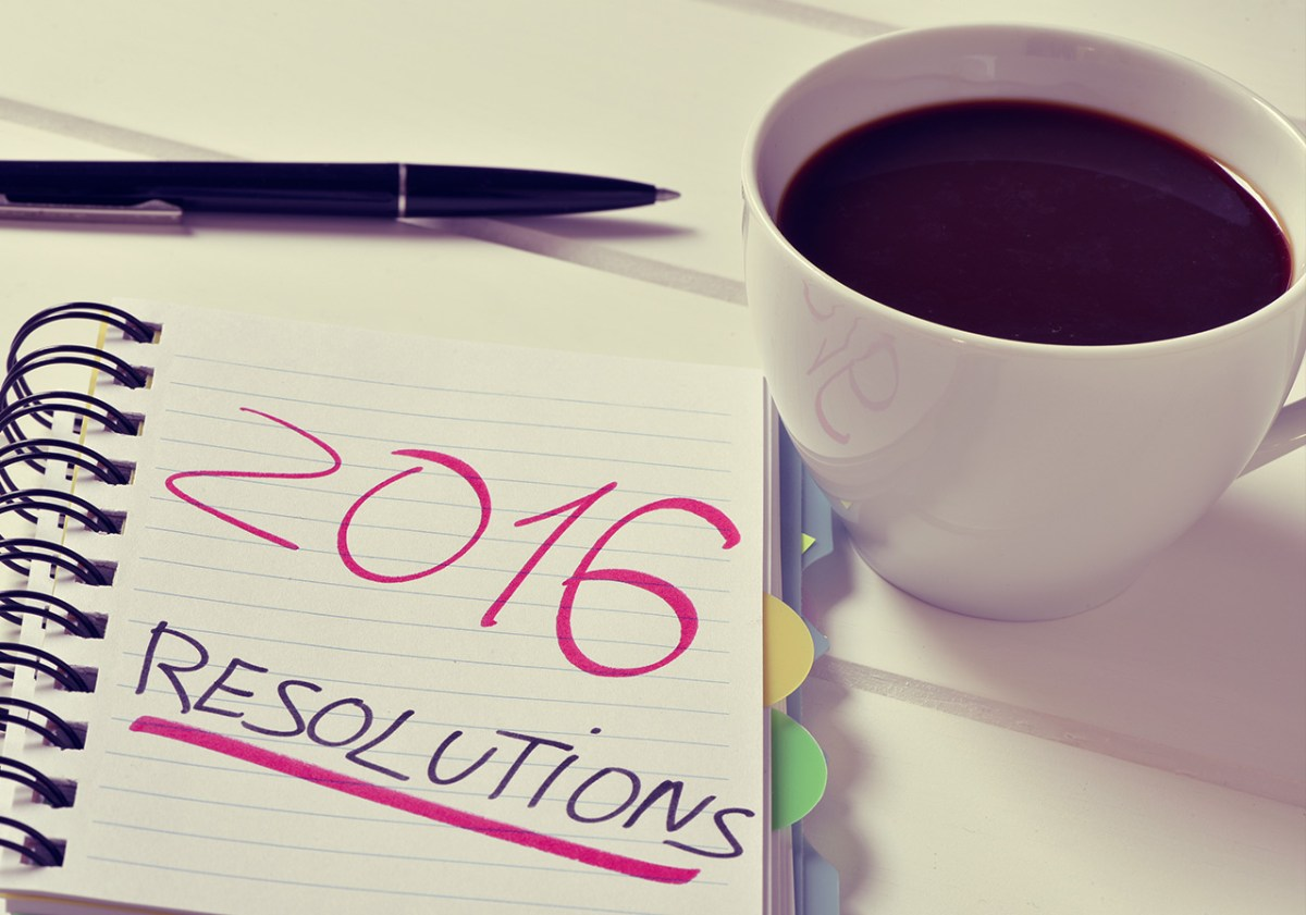 coffee pen and sign holder on desk - reads 2016 merchandising resolutions