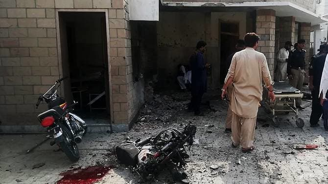 Pakistani security officials examine the site of a suicide bomb attack on Jul 21, 2019