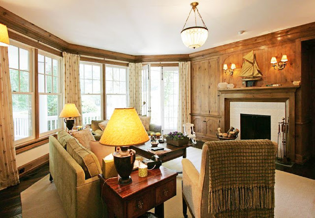 wood paneled family room/library with traditional decor, a fireplace and a pendant light