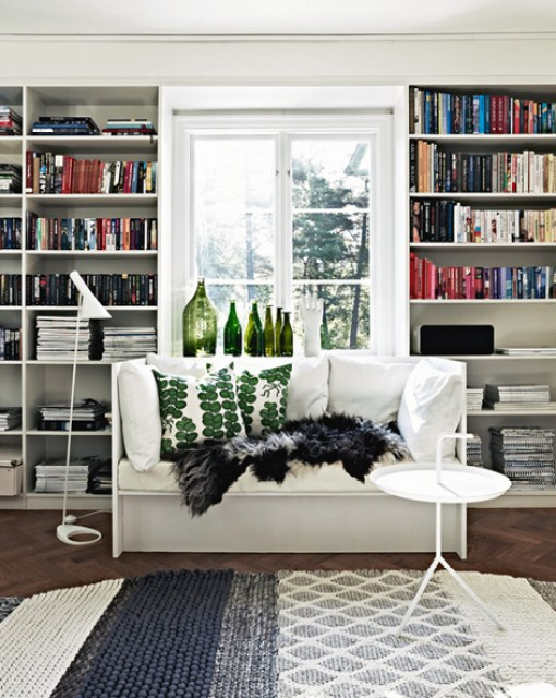 Home library white bench built in bookshelves green bottles grey rug herringbone wood floor