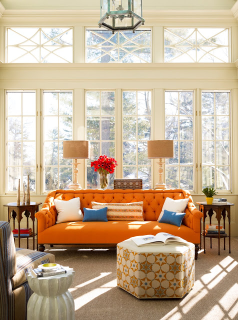 Living room with an orange sofa, tall windows, a hexagon ottoman, a striped armchair and Moroccan style side tables