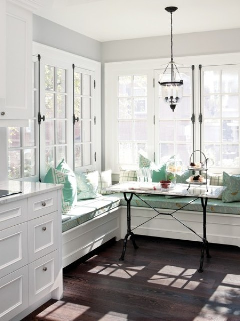 breakfast nook with sunny banquette built in windows, wood floors, white cabinets with turquoise pillows and cushions on the bench