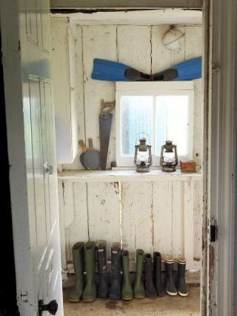 wellies in a rustic mudroom with lanterns