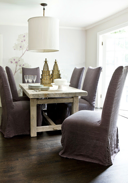 Formal dining room with light wood rough hewn table, linen upholstered Parsons chairs, floral wallpaper and oversized drum chandelier