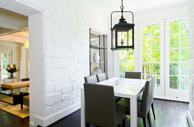 Breakfast nook with white stone walls, Parsons white lacquer table, french doors and a black lantern style pendant light