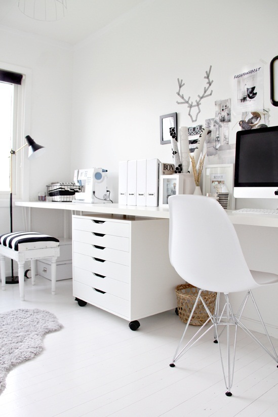 white home office with eames chair, white desk, white rolling chest of drawers with black accents in the form of pictures frames and a striped stool