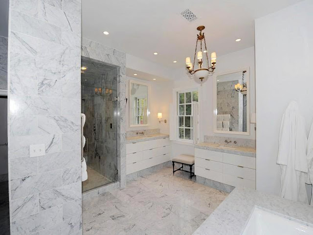 Master bathroom with marble floor, wall and counter tops, white drawers and a pendant light