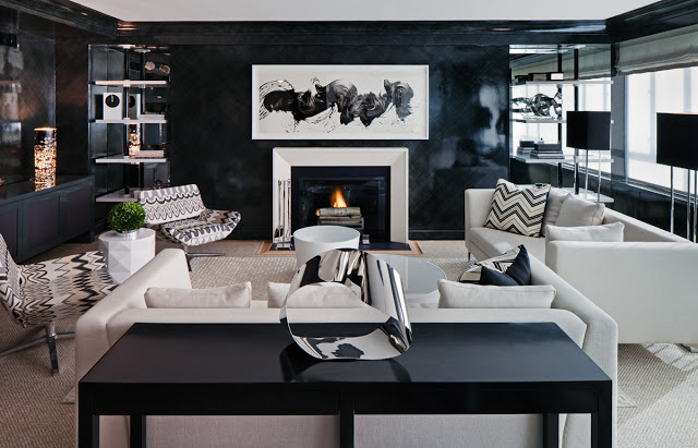 haus' interior living room with black lacquer wall paint, chevron pillows and upholstered lounge chairs, white sofas, fireplace with modern art hanging on the wall above it