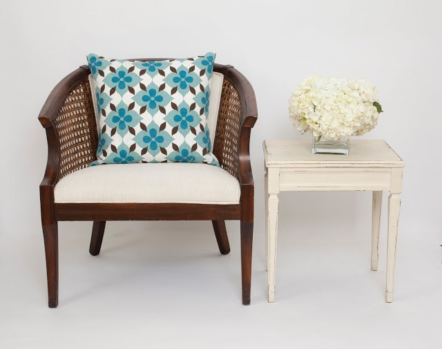 COCOCOZY Coco's Flower pillow on a classic cane chair next to a white vintage side table with white hydrangeas