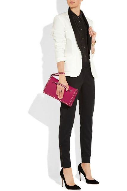 Model wearing black skinny pants, a white tuxedo jacket, black pumps and holding a pink Valentino Rockstud Clutch